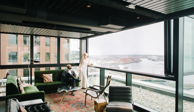 bride and groom resting in room that overlooks water and piers